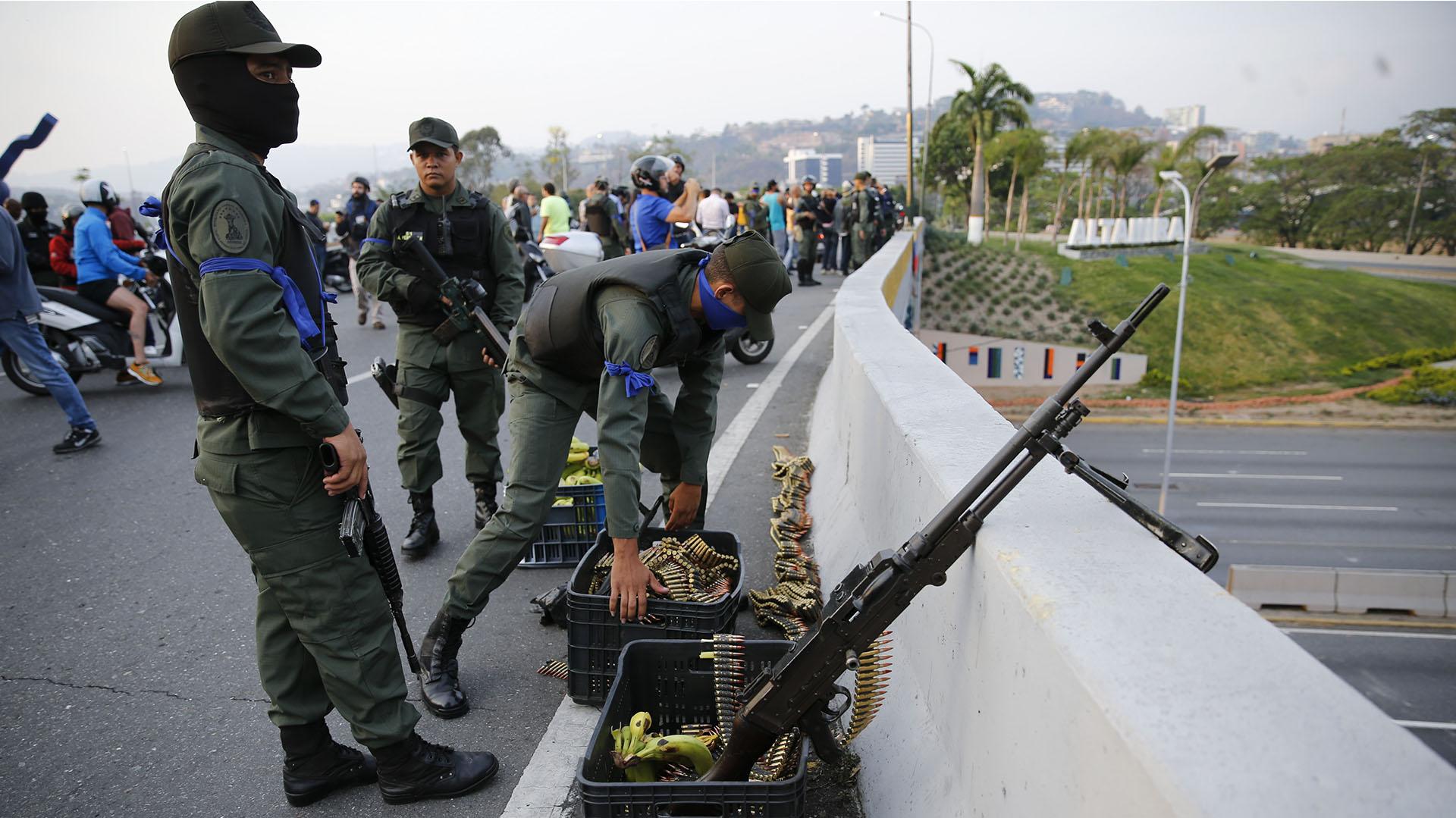 Los soldados de cinta azul se refugian en una autovía. (AP Photo/Ariana Cubillos)