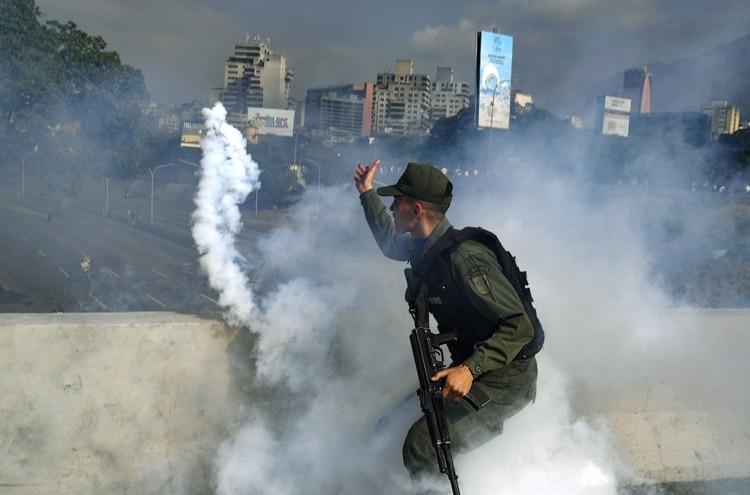 Un miembro de la Guardia Nacional Bolivariana que apoya al líder de la oposición venezolana y autoproclamado presidente en funciones, Juan Guaidó, lanza una lata de gas lacrimógeno durante un enfrentamiento con guardias leales al gobierno del presidente Nicolás Maduro frente a la base militar La Carlota en Caracas el 30 de abril de 2019.