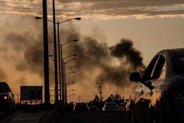 El humo de los autos incendiados se eleva en medio de un tiroteo en Culiacán, México, el jueves 17 de octubre de 2019. Un intenso tiroteo con armas pesadas y vehículos incendiados que bloqueaban las carreteras estalló en la capital del estado mexicano de Sinaloa el jueves pasado (Foto: AP/Augusto Zurita)
