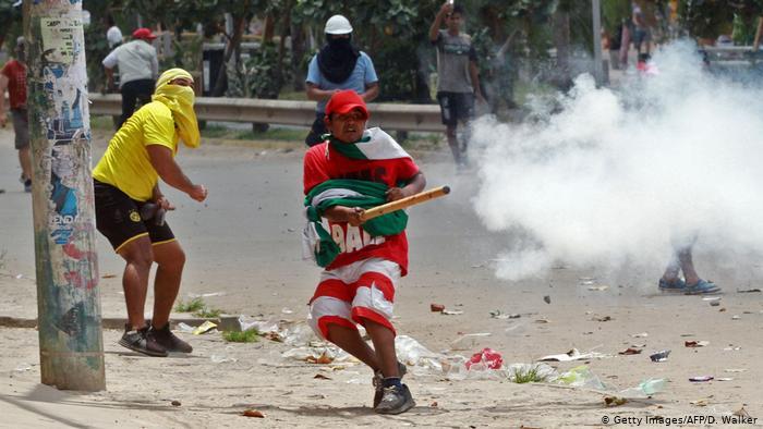 Foto de manifestantes enfrentándose en las calles de La Paz