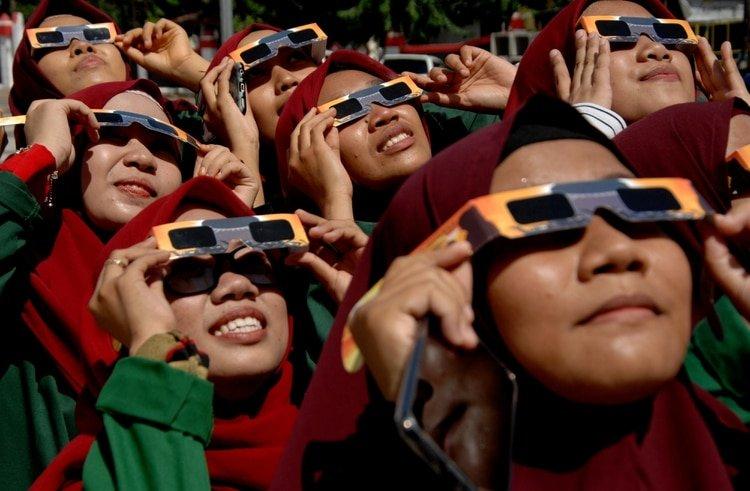 Mujeres usando unas gafas especiales para observar el eclipse (Antara Foto/Abriawan Abhe/via REUTERS)