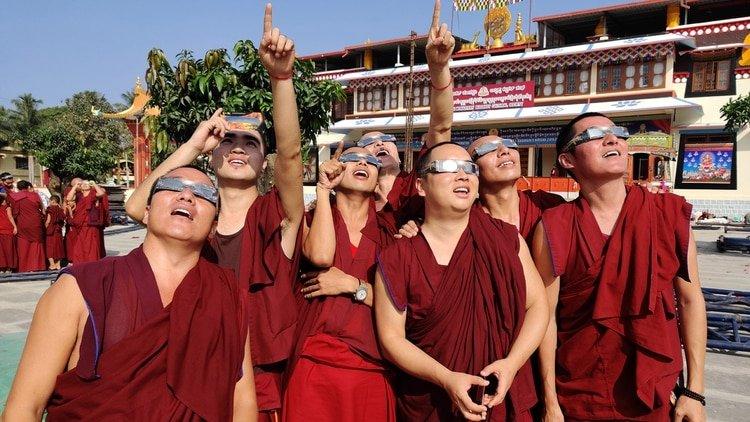 Los monjes observando el eclipse (Photo by Rakesh Nagar / AFP)