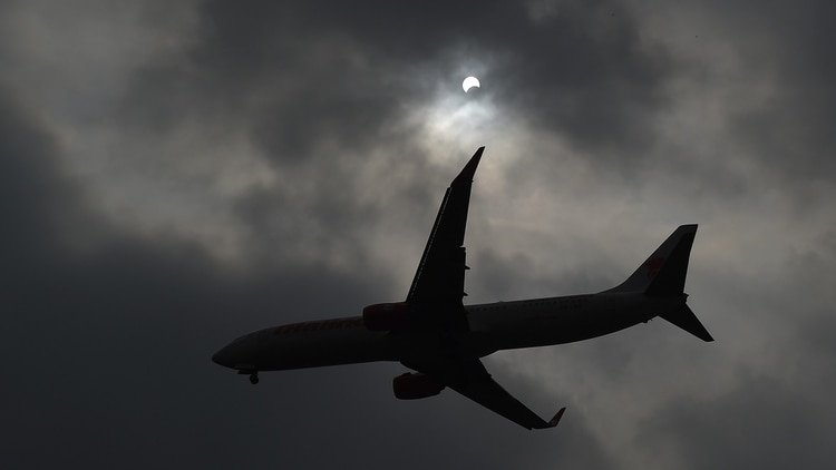 An airplane flies past as the moon moves in front of the sun in a rare