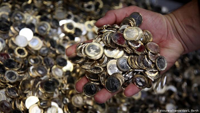Hand greift durch zahlreiche Ein-Euro-Münzen (picture-alliance/dpa/L. Barth)