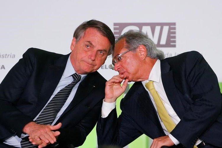 FOTO DE ARCHIVO: El presidente de Brasil, Jair Bolsonaro, escucha al ministro de Economía Paulo Guedes durante una reunión con empresarios en la Confederación Nacional de la Industria (CNI) en Brasilia. 11 de diciembre de 2019. REUTERS/Adriano Machado