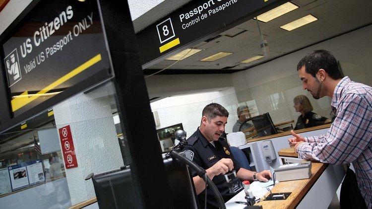 Un oficial de Aduanas y Protección Fronteriza revisa los pasaportes en la cabina de control de pasaportes cuando las personas ingresan a los Estados Unidos a través del Aeropuerto Internacional de Miami el 22 de junio de 2007 en Miami, Florida. (Photo by Joe Raedle/Getty Images)