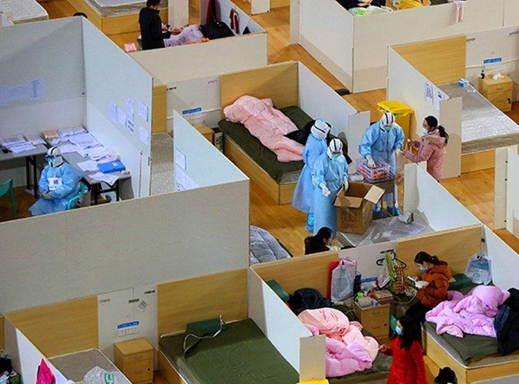 El personal médico vestido con trajes protectores distribuye comida en un estadio deportivo que se ha convertido en un hospital improvisado para tratar a los pacientes del nuevo coronavirus, en Wuhan, el 2 de marzo de 2020 (China Daily vía Reuters)