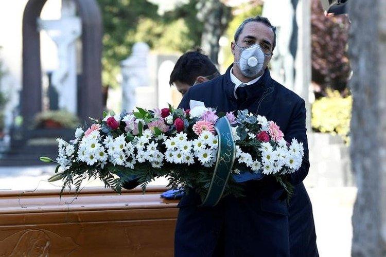 FOTO DE ARCHIVO. Trabajadores del cementerio y de una funeraria con mascarillas protectoras transportan un ataúd de una persona que murió por coronavirus (COVID-19), en Bérgamo, Italia. 16 de marzo de 2020. REUTERS/Flavio Lo Scalzo.