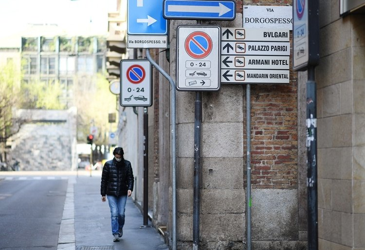Una mujer con una máscara facial protectora camina por una calle de Milán mientras continúa la propagación del coronavirus, el 21 de marzo de 2020. (REUTERS/Daniele Mascolo)