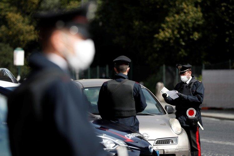 Carabineros italianos con máscaras protectoras verifican si un conductor tiene una razón válida para viajar durante el encierro en Roma, Italia, el 21 de marzo de 2020. (REUTERS/Yara Nardi)