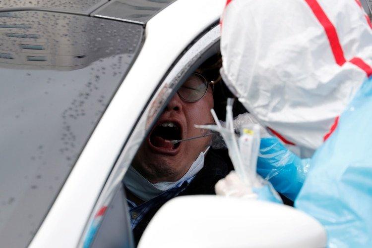 Personal médico utiliza un hisopo para tomar muestras de un conductor en el centro de pruebas de la Universidad de Yeungnam en Daegu, Corea del Sur, el 3 de marzo de 2020. (REUTERS/Kim Kyung-Hoon)