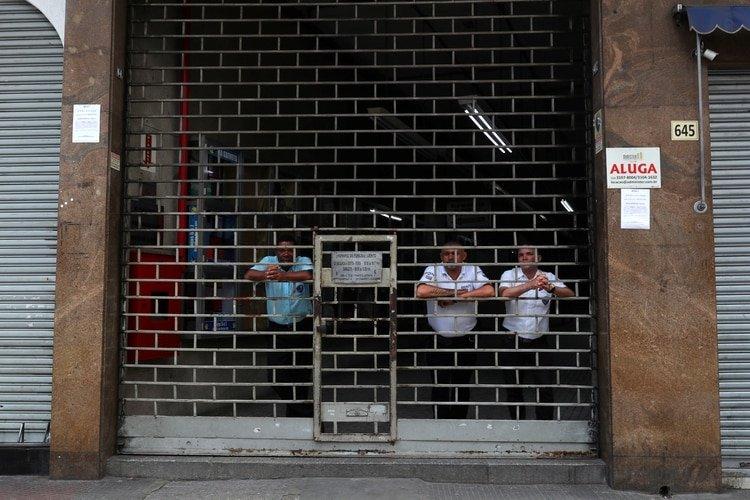 Guardias de seguridad vigilan una galería, cerrada tras la orden estatal (Reuters)