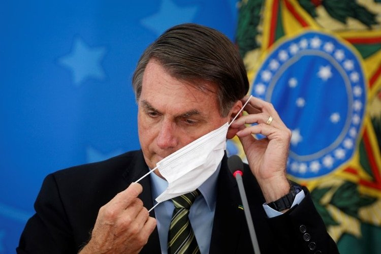 El presidente de Brasil, Jair Bolsonaro, ajusta su máscara facial protectora durante una conferencia de prensa para anunciar medidas judiciales federales para frentar la propagación de la enfermedad COVID-19, causada por el coronavirus, en Brasilia, Brasil. 18 de marzo, 2020. REUTERS/Adriano Machado
