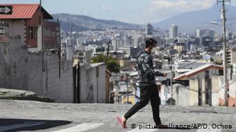 Foto de un hombre caminando con mascarilla en Quito