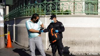 Foto de policía salvadoreño revisando a transeúnte