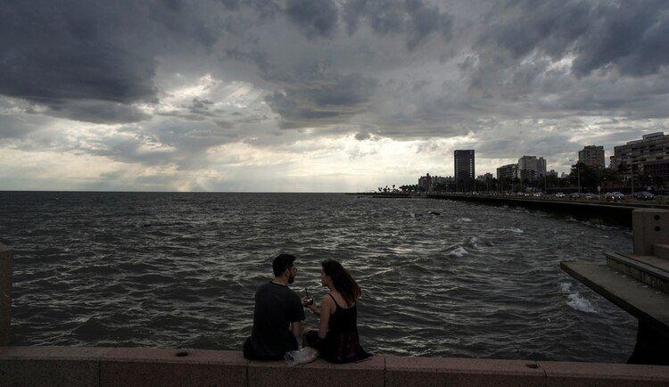 Una pareja comparte un mate en la Rambla de Montevideo (AFP)