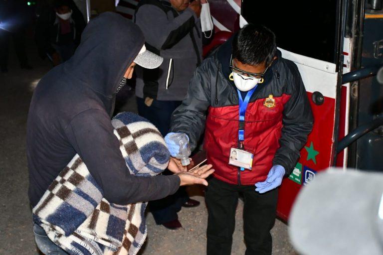 Un boliviano que cruzó la frontera por Pisiga, recibe una ración de alcohol en gel, antes de subir a un bus. Foto: Gobernación de Oruro.