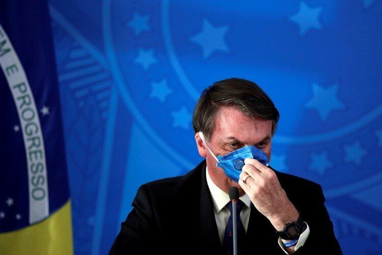 El presidente de Brasil, Jair Bolsonaro, ajusta su mascarilla protectora durante una conferencia de prensa sobre el brote de coronavirus, en Brasilia, Brasil. 20 de marzo de 2020. (REUTERS/Ueslei Marcelino)
