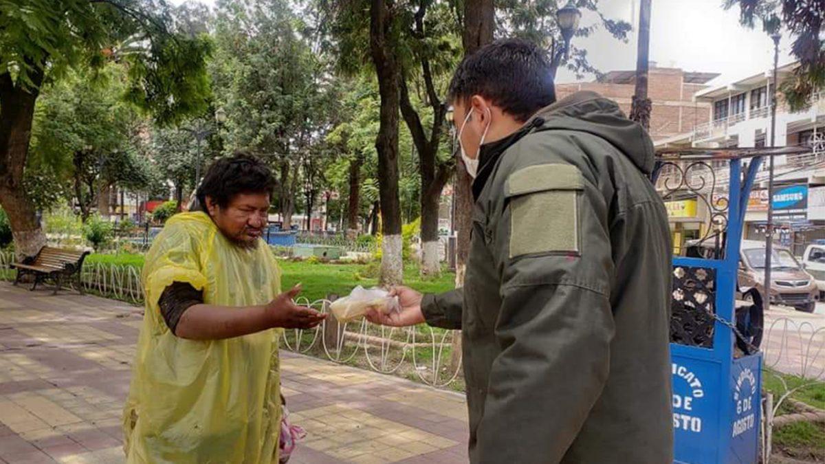 Policía da alimento a una persona en situación de calle. COMANDO REGIONAL POLICÍA VALLE BAJO