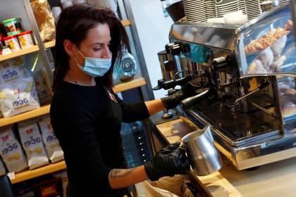 Una barista con un barbijo prepara un café en Trastevere, en Roma (REUTERS/Guglielmo Mangiapane)