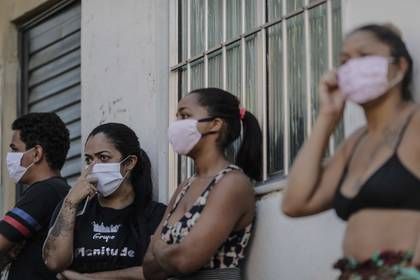 En la imagen se registró a un grupo de residentes de la favela de Mandela, en la zona norte de Río de Janeiro (Brasil), a la esperar de alimentos y ayudas, durante la actual pandemia por el COVID-19. EFE/Antonio Lacerda/Archivo