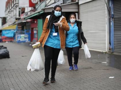 Mujeres caminas por la calle con mascarillas tras hacer las compras en Sparkhill, Reino Unido.