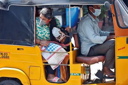 En India, una pasajera, su perro y el conducto de rickshaw utilizan barbijo.