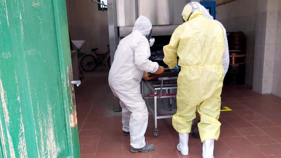 Dos trabajadores del Cementerio General introducen el cuerpo en el horno crematorio.