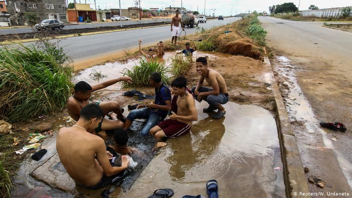 Jóvenes lavándose en un charco de agua en Caracas. (Archivo).