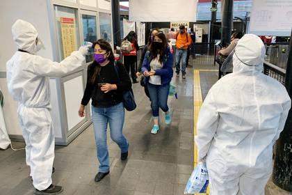 Usuarios del Metrobús pasan un filtro de seguridad y desinfección donde personal de Seguridad Pública, les toma la temperatura y les aplica gel antibacterial para poder ingresar a las instalaciones del sistema de transporte de Ciudad de México. EFE/José Pazos