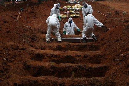 Sepultureros con trajes protectores entierran el ataúd de José Soares, de 48 años, quien murió a causa del coronavirus (COVID-19), en el cementerio de Sao Luiz, en San Pablo, Brasil (REUTERS/Amanda Perobelli)