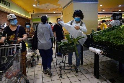 Personas usan mascarillas mientras compran verduras en un supermercado, después de los nuevos casos de infecciones de la enfermedad coronavirus (COVID-19) en Pekín, China, el 15 de junio de 2020. REUTERS/Tingshu Wang