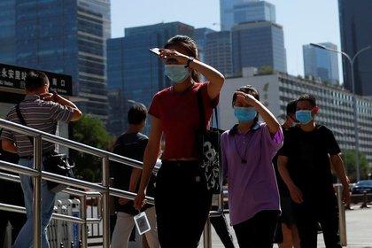 Personas usan mascarillas mientras se dirigen al trabajo durante la hora punta de la mañana, después de los nuevos casos de infecciones de la enfermedad coronavirus (COVID-19) en Pekín, China, el 15 de junio de 2020. REUTERS/Thomas Peter