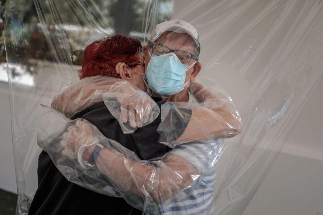 Una interna en una residencia de mayores en España abraza a su sobrino a través de un plástico.