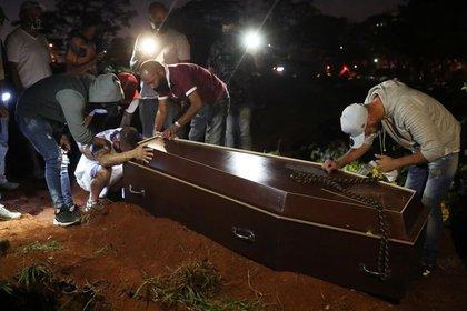 Un hombre reacciona junto el ataúd de su padre, que murió de la enfermedad coronavirus (COVID-19), antes de que lo entierren en el cementerio de Vila Formosa, el más grande de Brasil, en Sao Paulo. 19 de junio de 2020. REUTERS/Amanda Perobelli