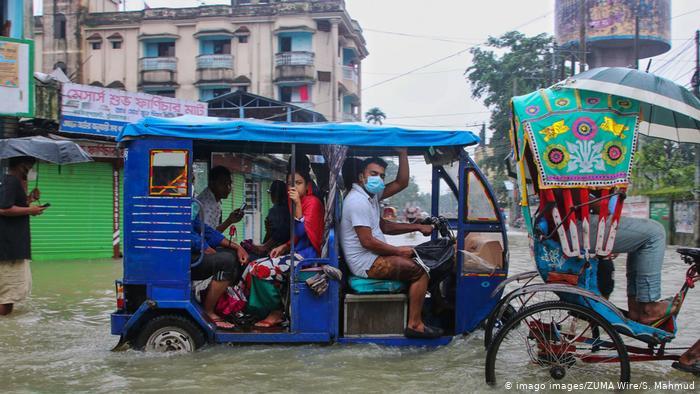 Foto de personas en calle inundada en Bangladesh