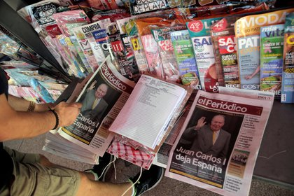 A man looks at the newspapers with news about Spain's former king Juan Carlos I, in Madrid, Spain August 4, 2020. REUTERS/Javier Barbancho