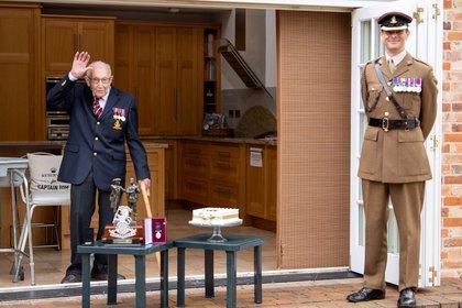 El ex oficial del ejército británico, el capitán Thomas Moore, nombrado primer coronel honorario del Army Foundation College en Harrogate, se encuentra con el teniente coronel Thomas Miller junto a sus medallas y regalos que recibió por su cumpleaños número 100 en Bedford, Gran Bretaña (Reuters)
