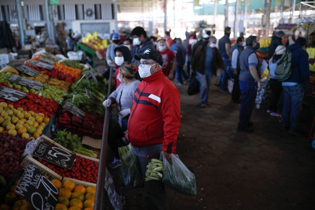 Personas con tapabocas hacen compras en el Mercado Central de Frutas y Verduras de la provincia de Buenos Aires, Argentina.