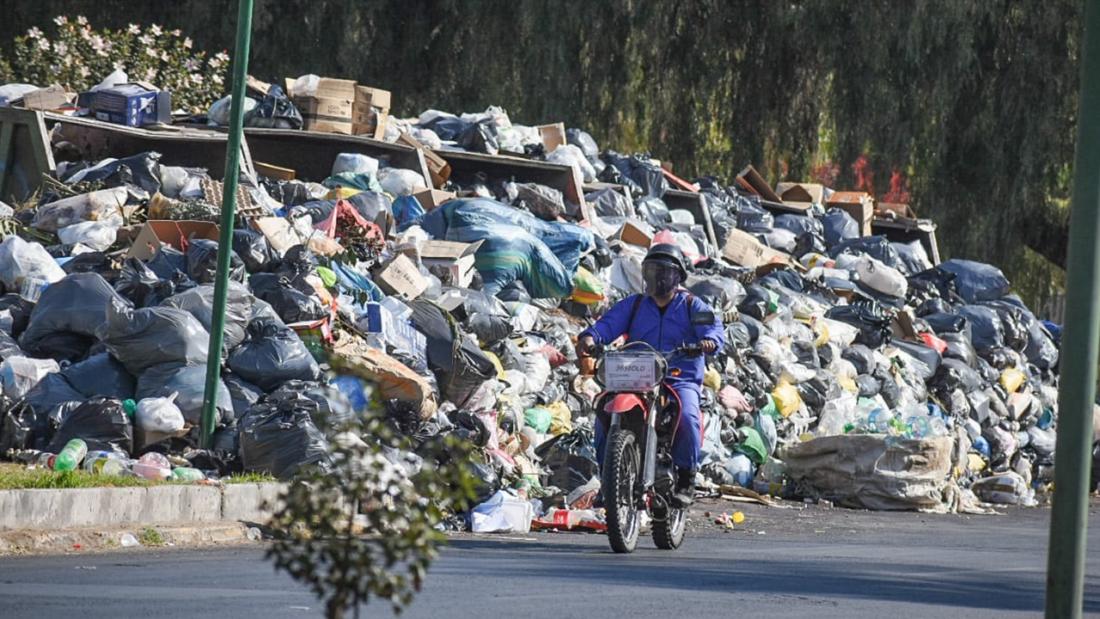 """Un conductor de motocicleta pasa por una """"montaña"""" la basura en la ciudad."""