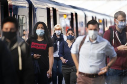 Pasajeros con mascarillas en la estación Waterloo de Inglaterra, donde su uso es obligatorio (Victoria Jones/PA Wire/dpa)
