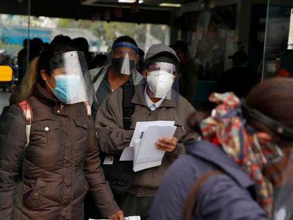 FOTO DE ARCHIVO. Personas con mascarillas y protectores faciales hacen fila antes de abordar autobuses, durante el brote de la enfermedad por coronavirus (COVID-19), en Lima, Perú. 15 de julio de 2020. REUTERS/Sebastián Castañeda