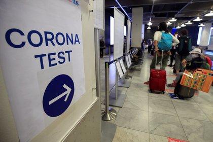 Pasajeros en fila para someterse a una prueba de Covid-19 en el aeropuerto de Duesseldorf, en Alemania (REUTERS/Wolfgang Rattay)