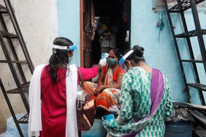 Voluntarios comunitarios de salud controlan la temperatura de una mujer durante una campaña de control de coronavirus en un barrio pobre de Mumbai, India, el 16 de agosto de 2020. (REUTERS / Francis Mascarenhas)