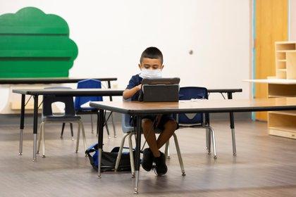 Un estudiante asiste a una clase virtual mientras es monitoreado por asistentes de instrucción cuando se reanuda el aprendizaje en una escuela primaria en Phoenix, Arizona (Reuters)