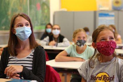 Alumnas de quinto año usan voluntariamente máscaras protectoras dentro de su aula cuando las escuelas vuelven a abrir después de las vacaciones de verano en la escuela secundaria Karl-Rehbein en Hanau, Alemania (Reuters)