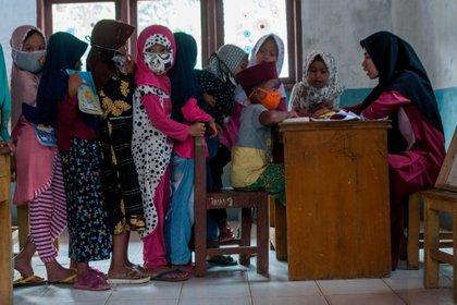 Niños con mascarillas protectoras hacen fila durante las actividades de enseñanza y aprendizaje en medio del brote de coronavirus en Lebak, provincia de Banten, Indonesia (Reuters)