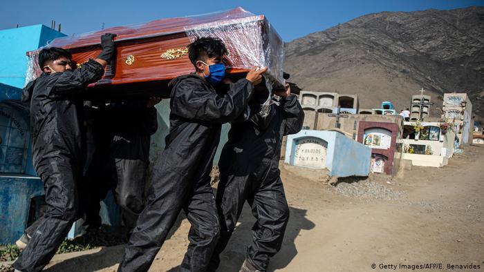 Trabajadores del cementerio de Comas, en el norte Lima, transportan ataúdes de personas fallecidas por COVID-19.