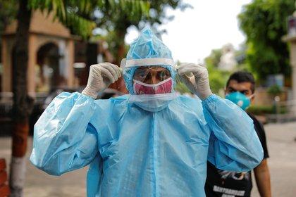 Un hombre que usa equipo de protección personal (PPE) ajusta su protector facial antes de la cremación de un familiar que murió debido a la enfermedad coronavirus (COVID-19), en un crematorio en Nueva Delhi, India, el 22 de agosto de 2020. REUTERS/Adnan Abidi