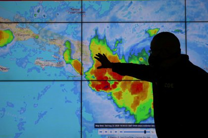 Un miembro del Comité de Operaciones de Emergencia mira la trayectoria de Laura en su paso por Santo Domingo, República Dominicana (REUTERS/Ricardo Rojas)